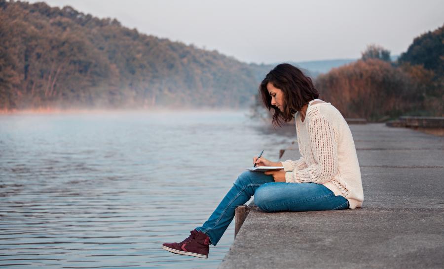 Junge Frau mit Skizzenbuch am See