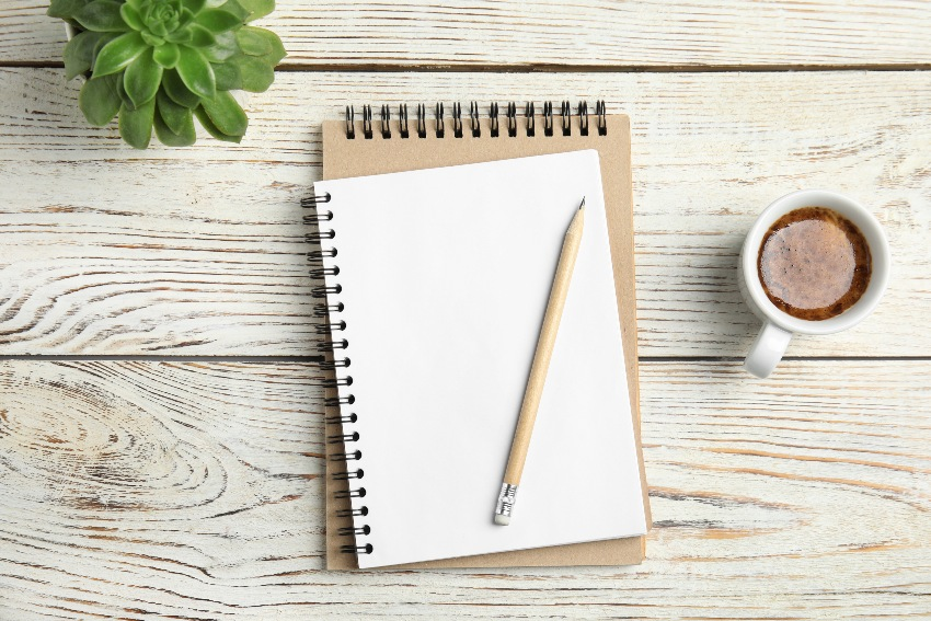 Zwei Notizblöcke mit einer Tasse und einem Bleistift
