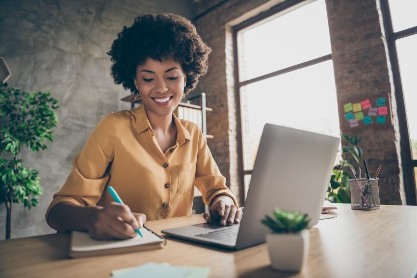 Frau am Schreibtisch mit Laptop und Notizblock