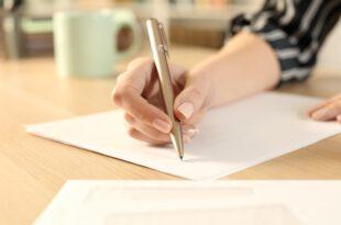 Mensch schreibt mit Kugelschreiber