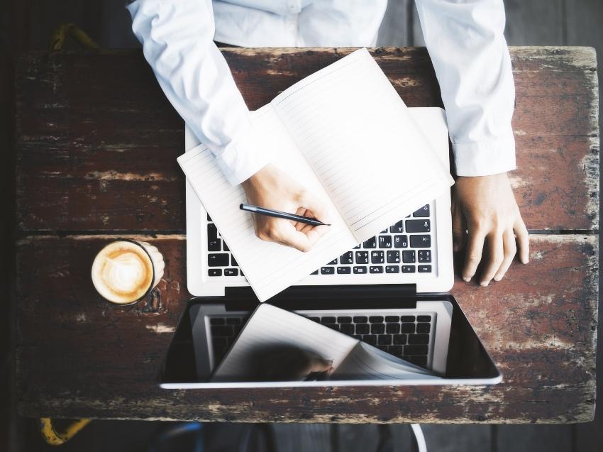 Aufsicht von einem Mann mit Laptop und Notizbuch am Tisch