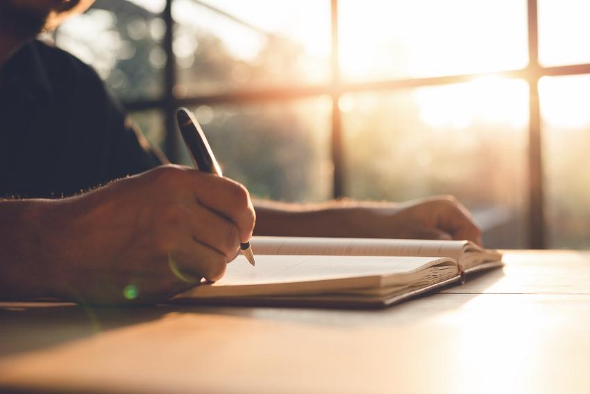 Eine Person, die in ein Notizbuch schreibt