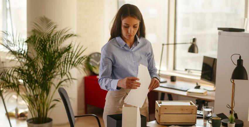 Frau beim Sortieren des Schreibtischs