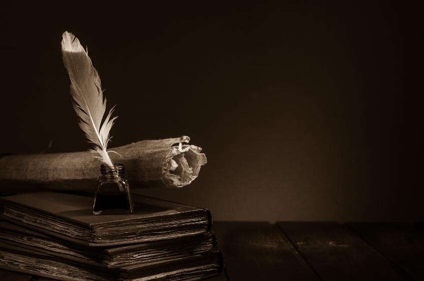 Feder und Tinte auf einem Stapel Bücher