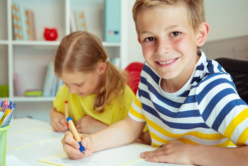 Junge und Mädchen mit Schreiblernfüllern