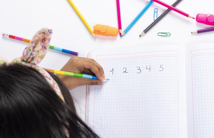 Junge Linkshänderin schreibt Zahlen in einen Schreibblock - Linkshänder müssen heutzutage nicht mehr umlernen