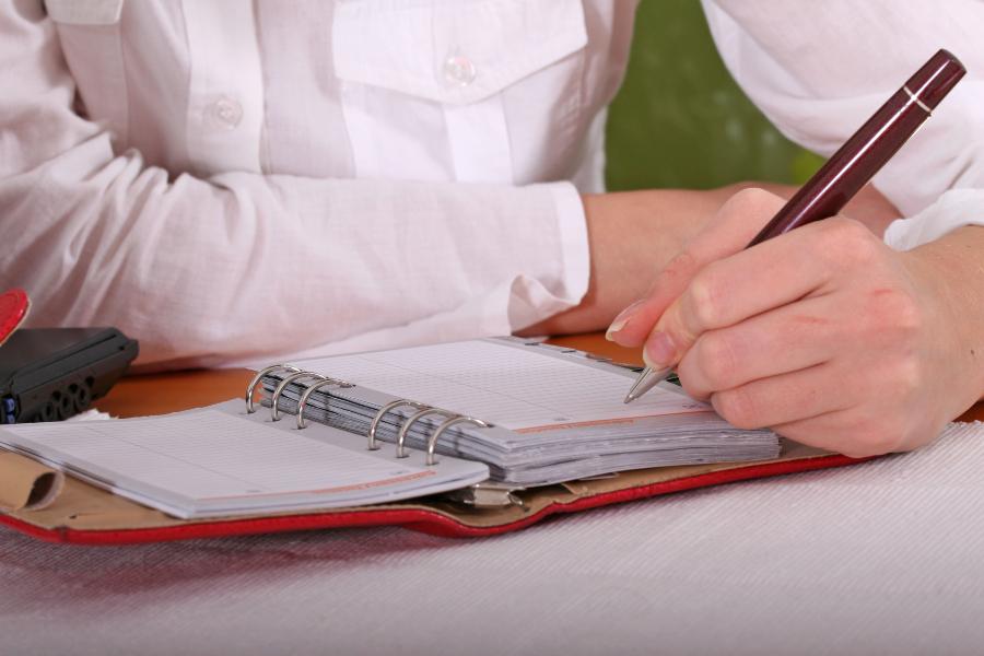 Person schreibt mit linker Hand in einen Terminkalender