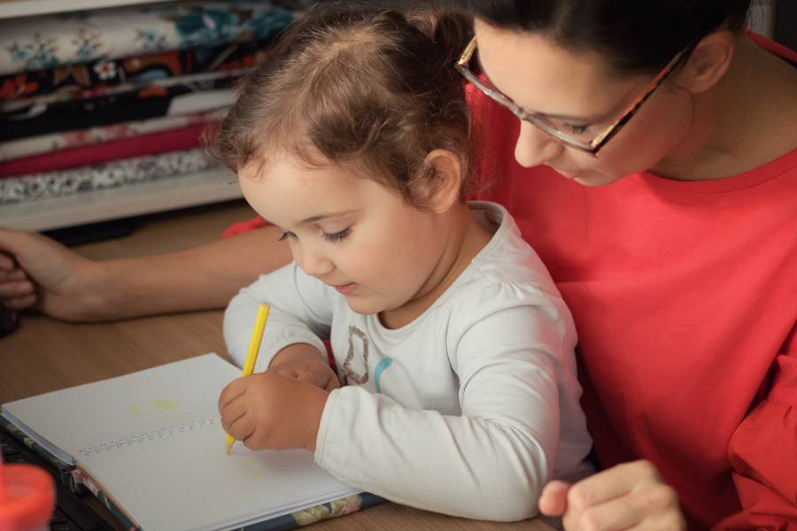 Kleines Mädchen auf Schoß der Mutter malt mit linker Hand - ob Linkshänder oder Rechtshänder spielt keine große Rolle
