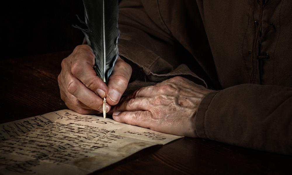 Mann schreibt mit Federkiel - mittelalterliches Ambiente