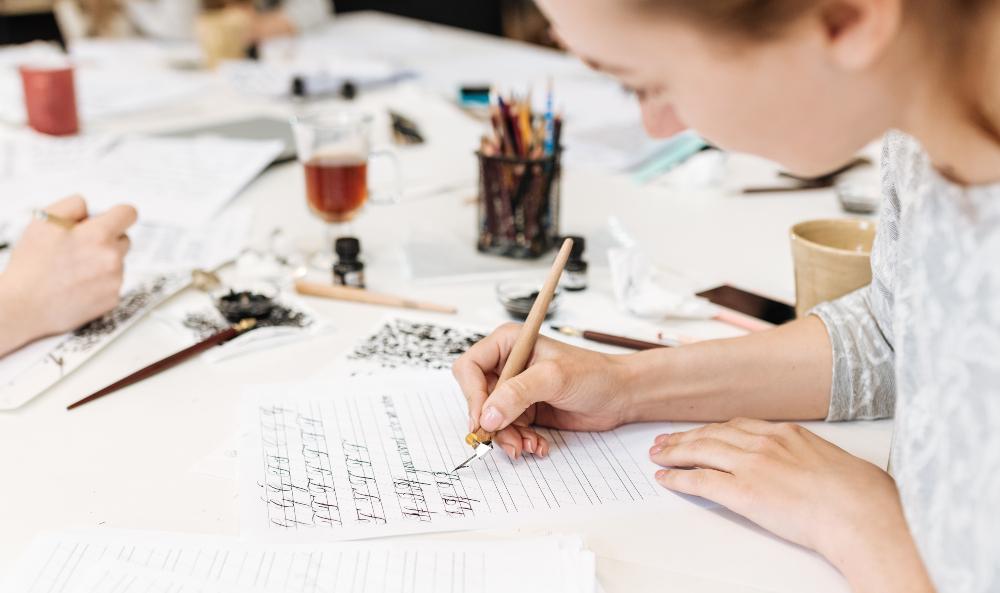 Junge Frau schreibt auf Blatt mit Hilfslinien