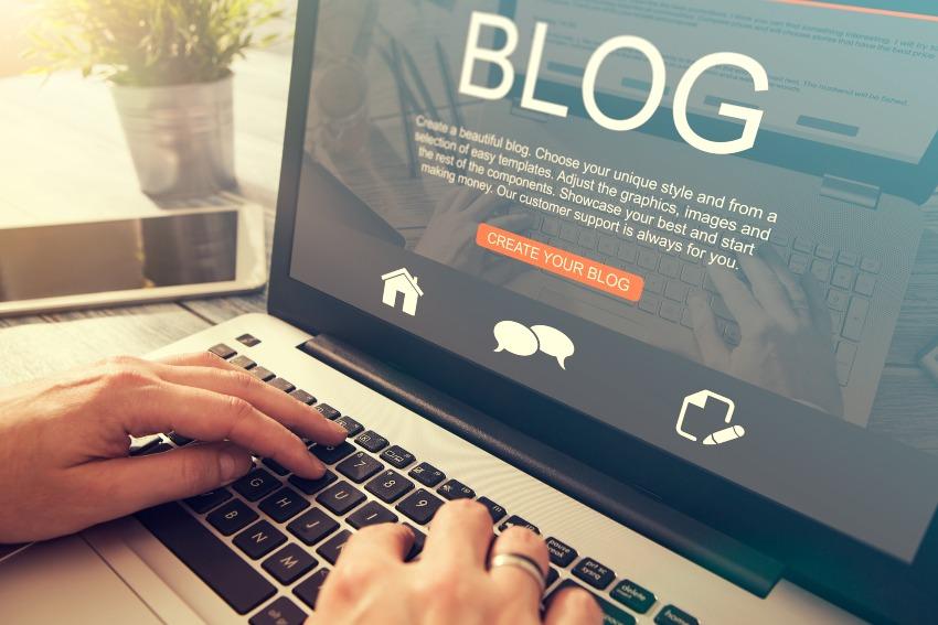 Jemand schreibt Blog an einem Laptop