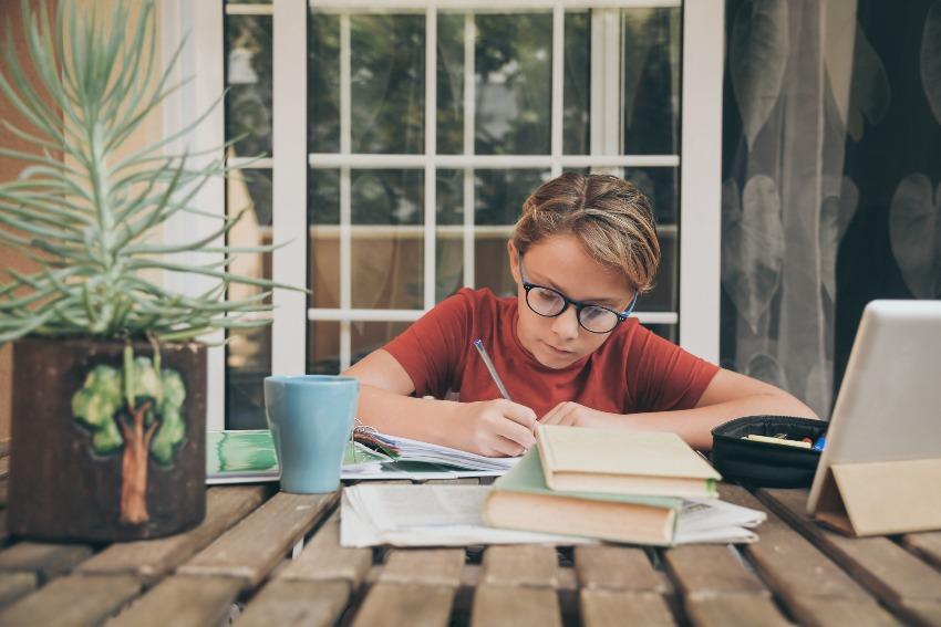 Junge schreibt in ein Buch/Heft - kreatives Schreiben