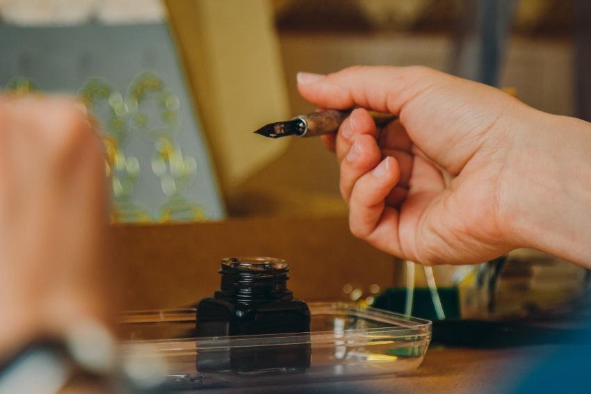 Person hält ihren Füllfederhalter über einem Tintenfass - Konverter und Kolbenfüller