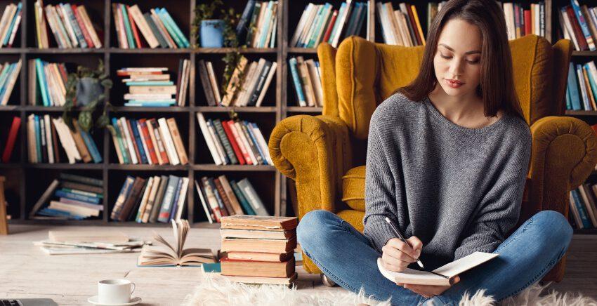 Junge Frau schreibt in Notizbuch - Design-Stifte