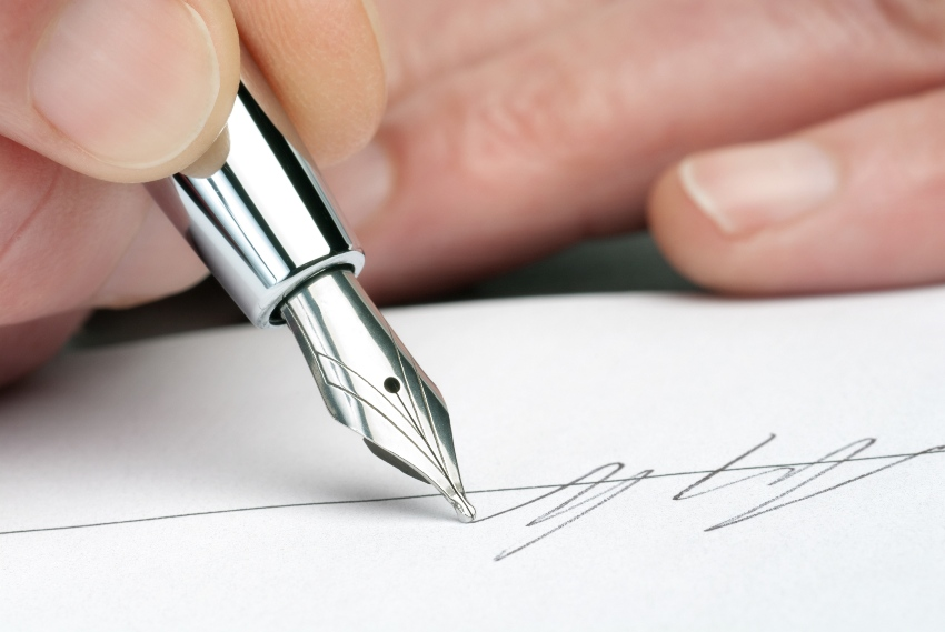 Jemand unterschreibt mit einem Füllfederhalter