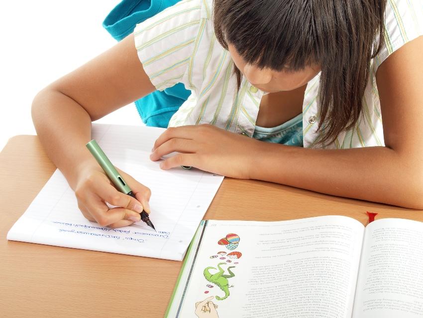 Junge Schülerin schreibt in Schreibschrift